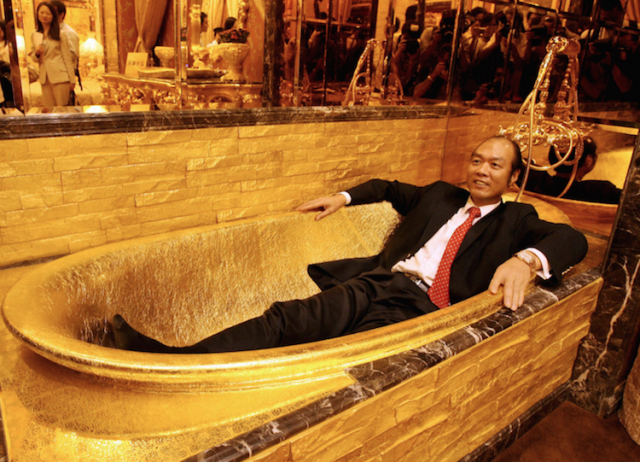 A man lounging in a solid-gold bathtub -- possibly relaying that he's a bad tipper