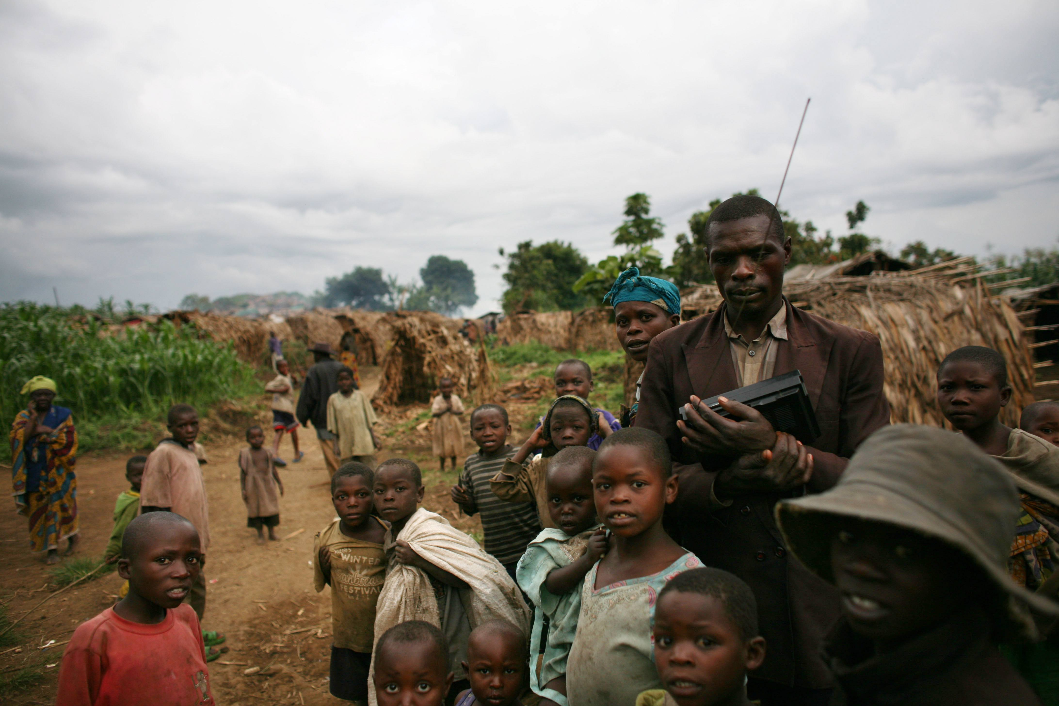 Refugees wait near their shelters in the Democratic Republic of the Congo