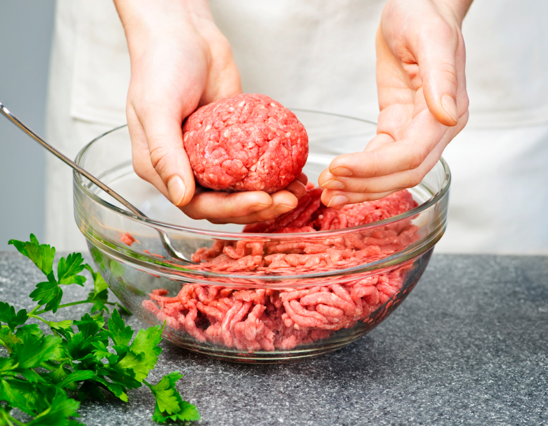 person's hands in a bowl of ground beef making meatballs
