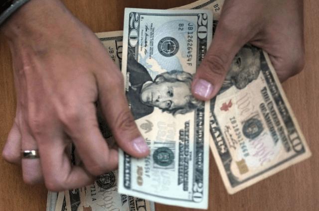Man holding 20-dollar bills.