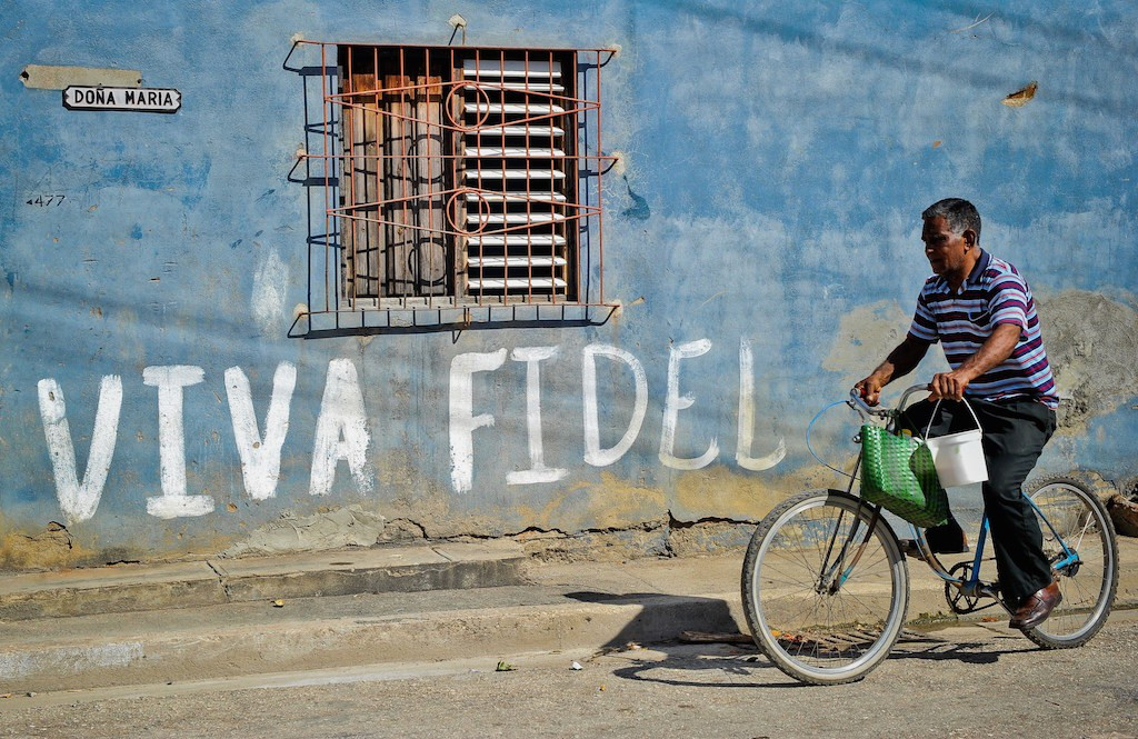A Cuban rides his bicycle by a graffiti hailing Cuban former president Fidel Castro, on August 12, 2014 in Havana. (Photo by Yamil Lage/AFP/Getty Images)