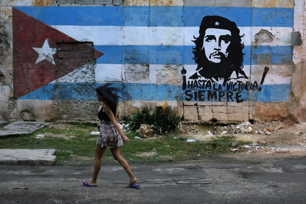 A young woman walks past a mural dipicting Cuban revolutionary leader Che Guevarra in the Jesus Maria neighborhood January 24, 2015 in Havana, Cuba. Diplomats from the United States and Cuba held historic talks this week that could restore diplomatic ties and mark the end of more than 50 years of of Cold War-era hostility between the two countries. (Photo by Chip Somodevilla/Getty Images)