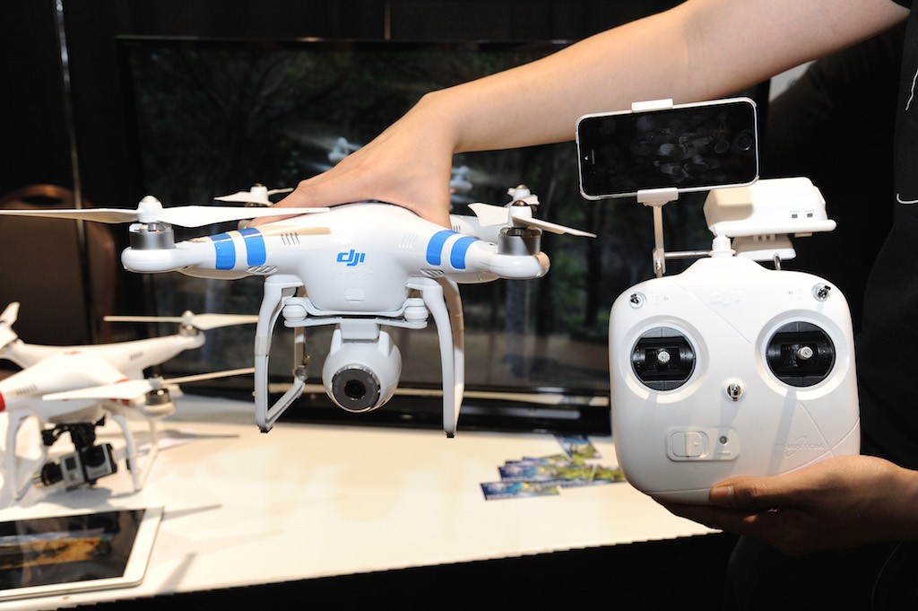 A DJI Innovations DJI Phantom 2 Vision aerial system drone with controller (R) is shown during 'CES: Unveiled,' the media preview for International CES, at the Mandalay Bay Convention Center January 5, 2014 in Las Vegas, Nevada. The Phantom 2 Vision, available for USD 1,199, has a 14-megapixel camera on board that can shoot raw photos and 1080p video. The video can be seen live and stored on an iPhone or Android smart phone attached to the controller. (Photo by Robyn Beck/AFP/Getty Images)
