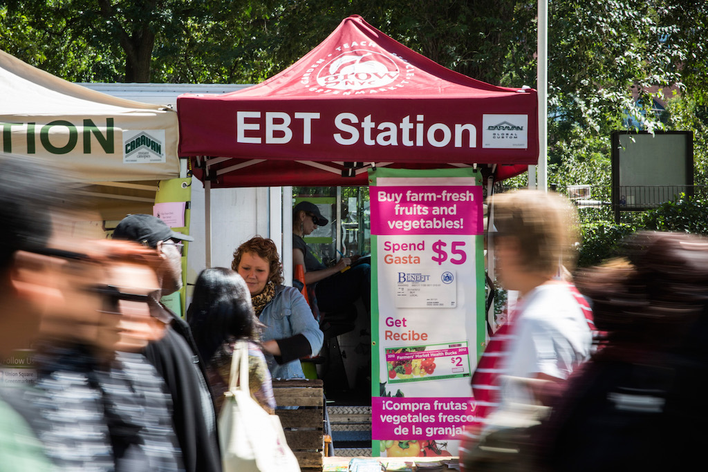 People walk past an Electronic Benefits Transfer (EBT) station, more commonly known as Food Stamps, in the GrowNYC Greenmarket in Union Square on September 18, 2013 in New York City. According to a Gallup poll released earlier this month, 20% of American adults struggled to buy enough food at some point in the last year. The rate of hungry people in America has gone relatively unchanged since 2008, suggesting the economic recovery since the 2008 recession may be disproportionately affecting the wealthy. More than 50 of GrowNYC's Greenmarket's now accept EBT; over $800,000 in sales were complete with EBT payment at the Greenmarket's in 2012. GrowNYC is also currently offering a program known as Health Bucks: for ever $5 spent using EBT at a Greenmarket, GrowNYC provides an additional $2, which can be spent specifically on fresh fruits and vegetables. (Photo by Andrew Burton/Getty Images)