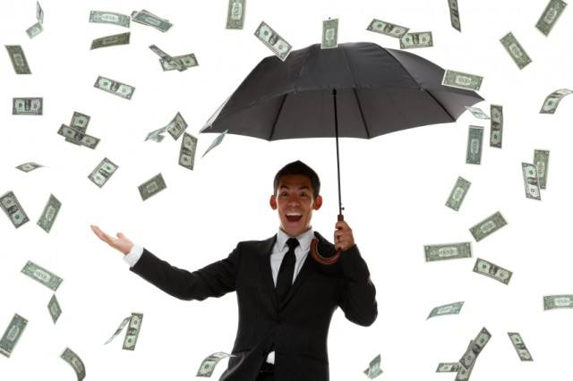 Man holding umbrella with money falling from sky.