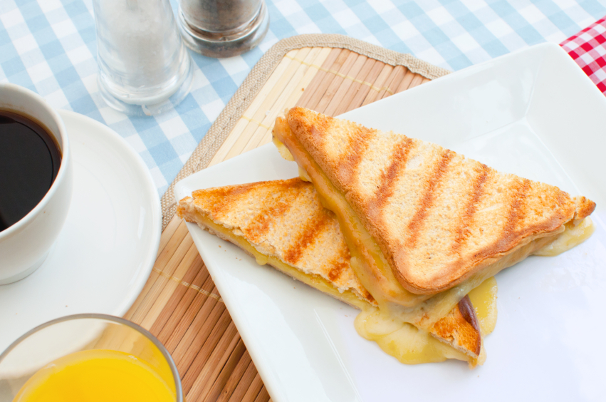 Grilled cheese sandwich on a platter along with coffee and orange juice