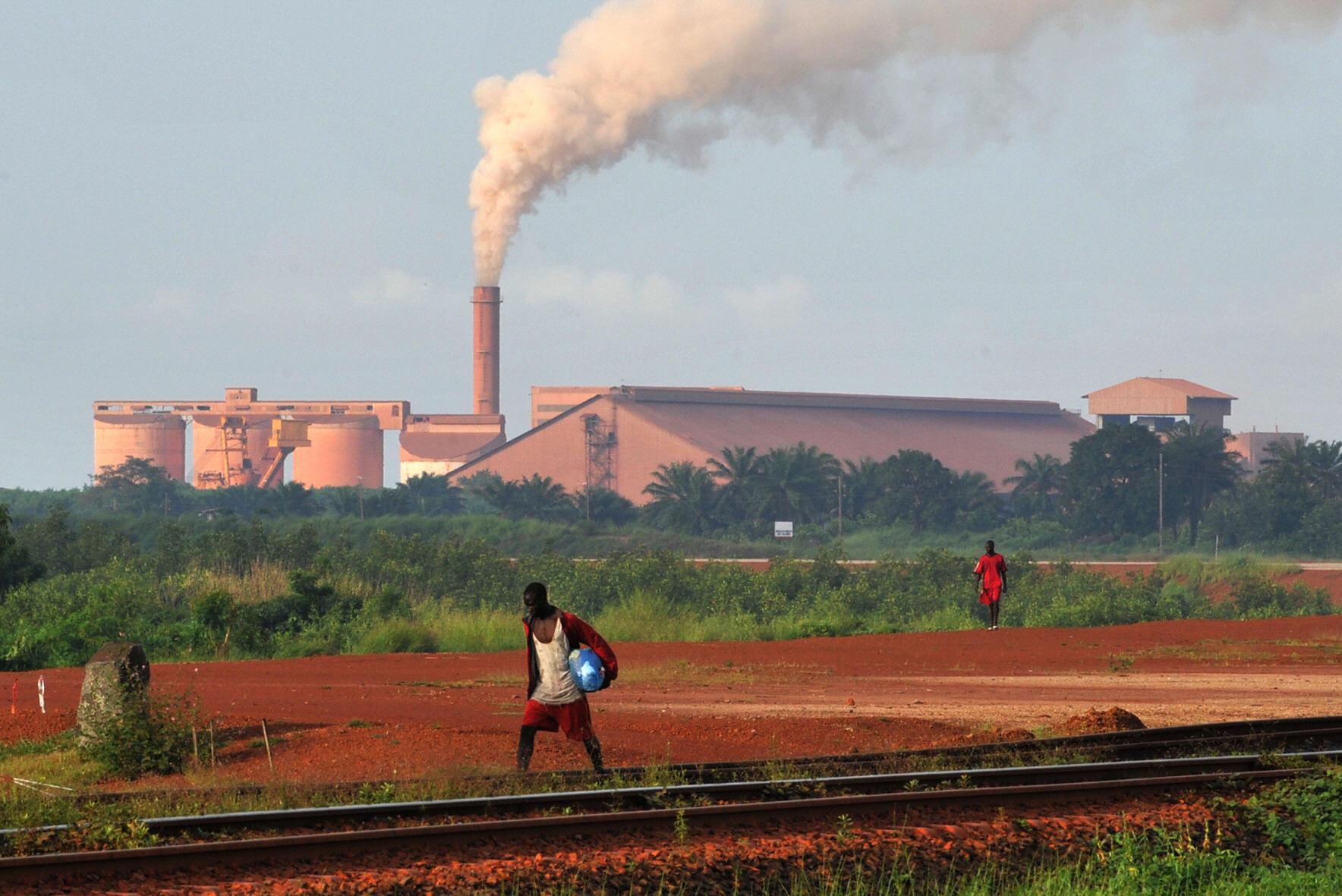 A man walks on rail tracks near a Guinea factory