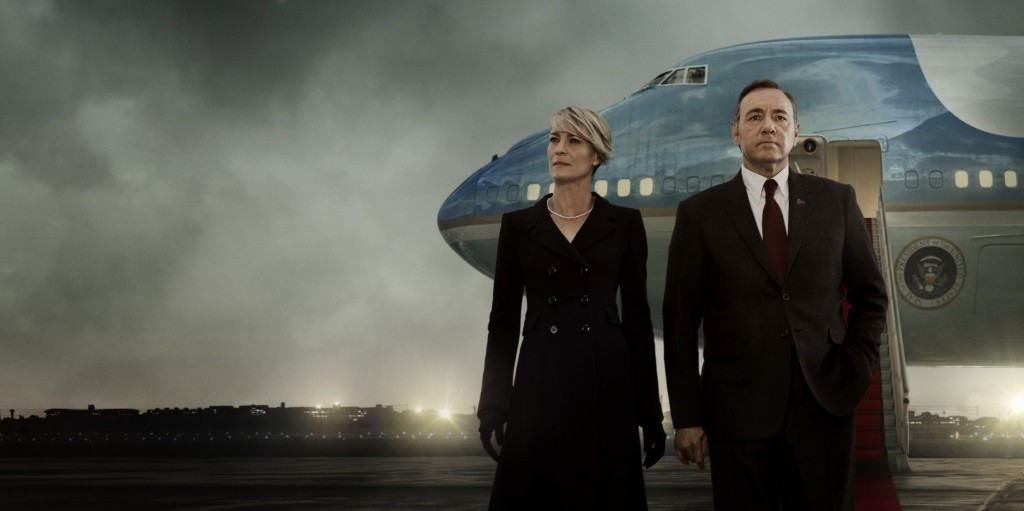 Kevin Spacey and Robin Wright stand on a tarmac outside of a plane in House of Cards