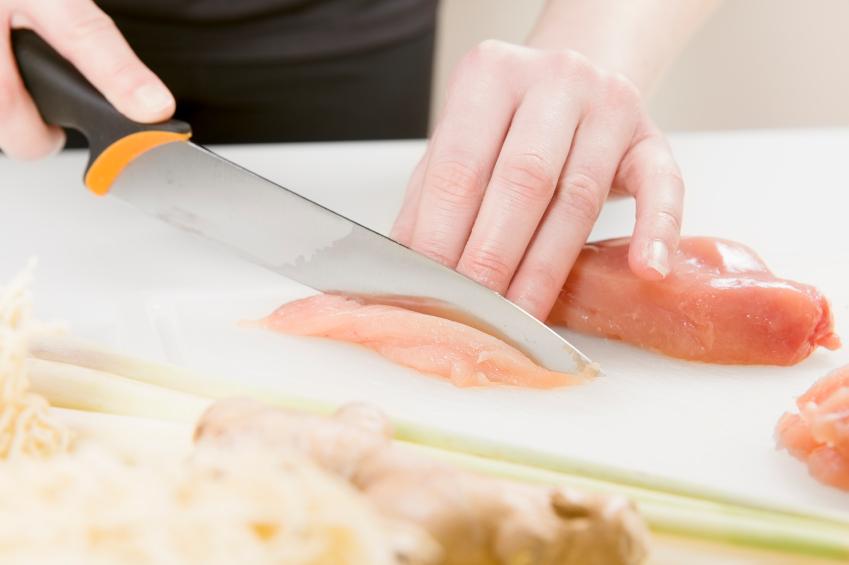 cutting chicken on a cutting board