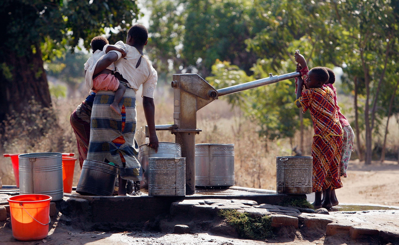 Children pump water in Ligwangwa, Malawi