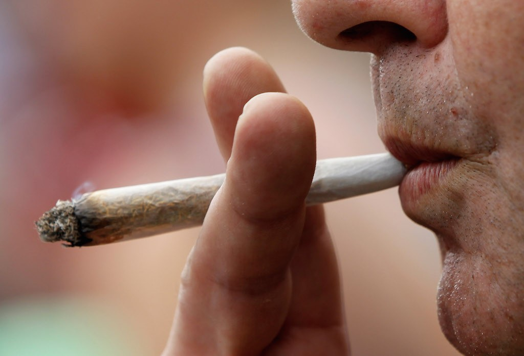 A man smokes licenced medicinal marijuana prior to participating in the annual Hemp Parade, or 'Hanfparade', in support of the legalization of marijuana in Germany on August 7, 2010 in Berlin, Germany. The consumption of cannabis in Germany is legal, though all other aspects, including growing, importing or selling it, are not. However, since the introduction of a new law in 2009, the sale and possession of marijuana for licenced medicinal use is legal. (Photo by Sean Gallup/Getty Images)