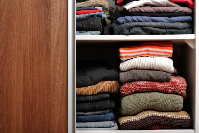 folded clothes in an open wardrobe