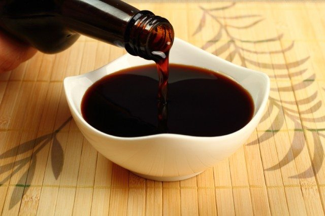 pouring soy sauce into a white dish