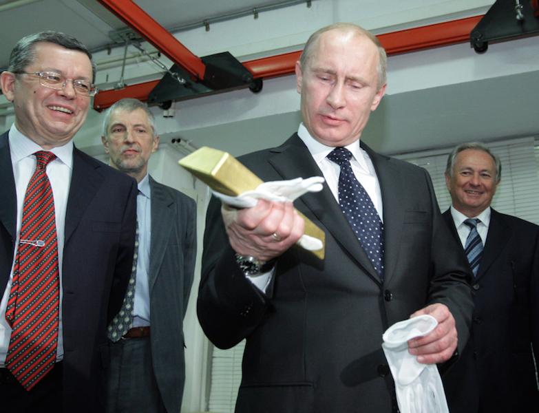 Russia president Vladamir Putin holding a gold bar
