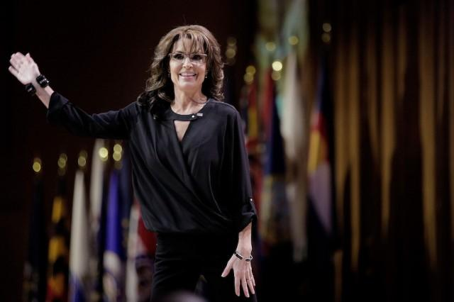 Sarah Palin waves at a crowd while walking across a stage.