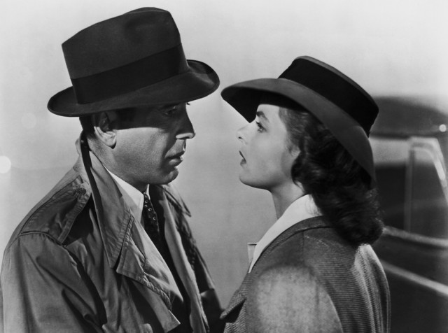A black and white still of a man and woman staring at each other