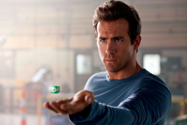 Ryan Reynolds stares ahead and holds up a green ring in The Green Lantern