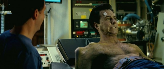 Edward Norton lays on a bed and grimaces in The Incredible Hulk