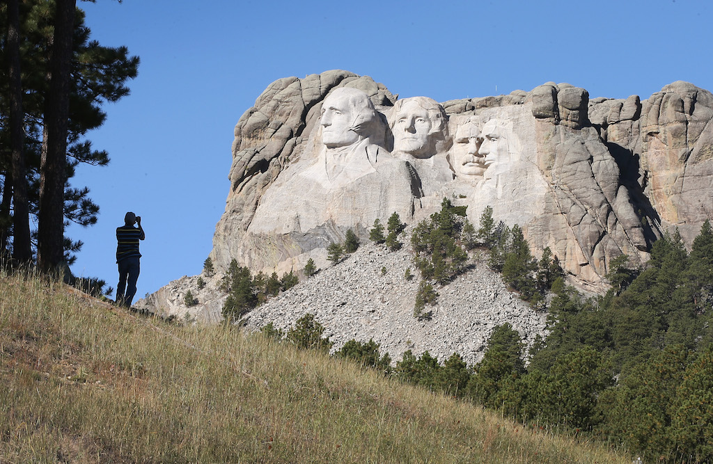 A tourist takes a picture of Mount Rushmore National Memorial from outside the park