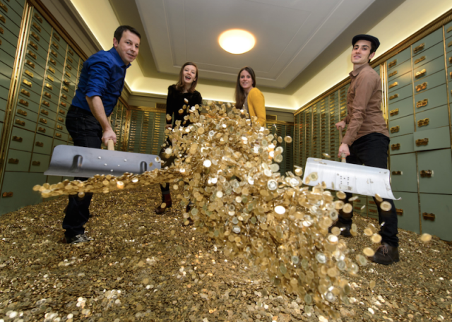 Young people in a bank vault shoveling gold coins
