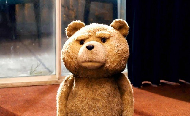 A grumpy-looking teddy bear stands in front of a door