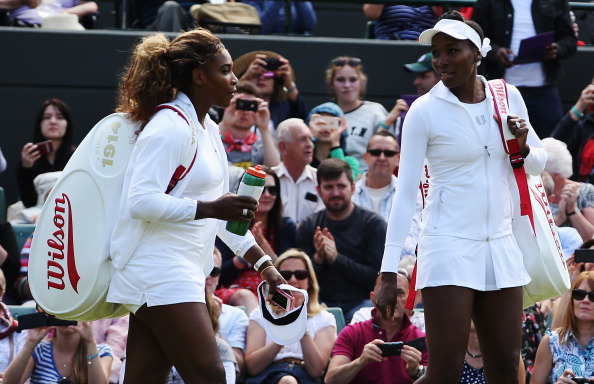 Serena and her sister stand in a tennis court in front of a crowd.