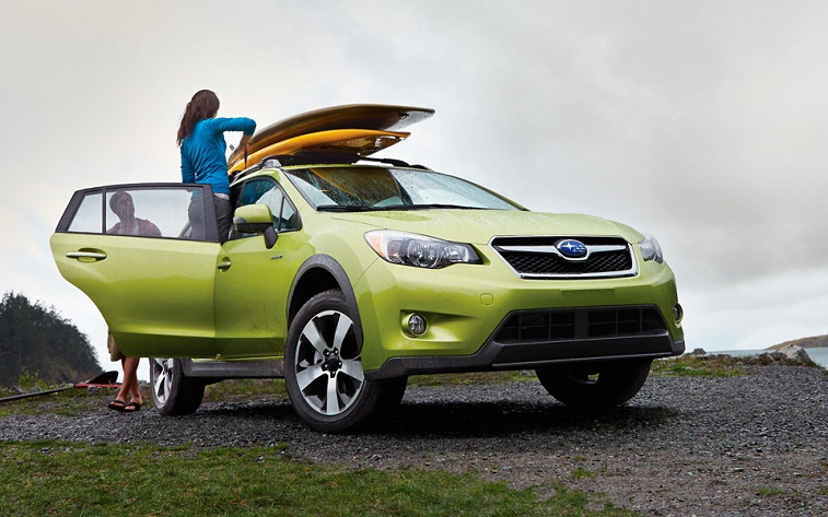 A man and woman load surfboards on top of a Subaru XV Crosstrek Hybrid.