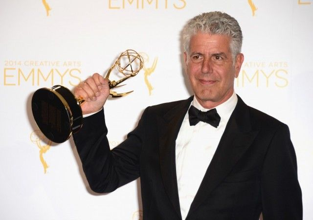Anthony Bourdain holding an Emmy award.