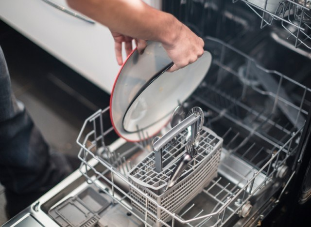 man loading dishes in dishwasher