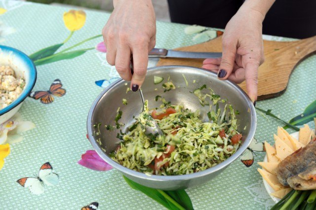 Stirring cabbage coleslaw with tomatoes, cucumber