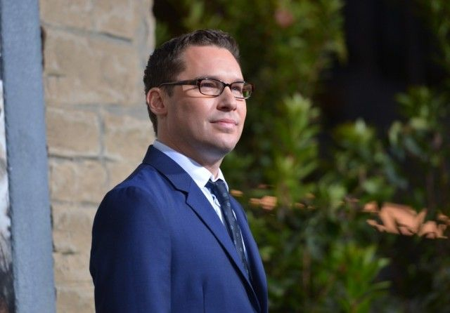 Bryan Singer, wearing a blue suit and glasses, looking to the right of the frame.