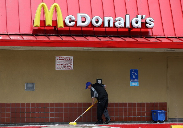 man sweeping outside of a McDonald's