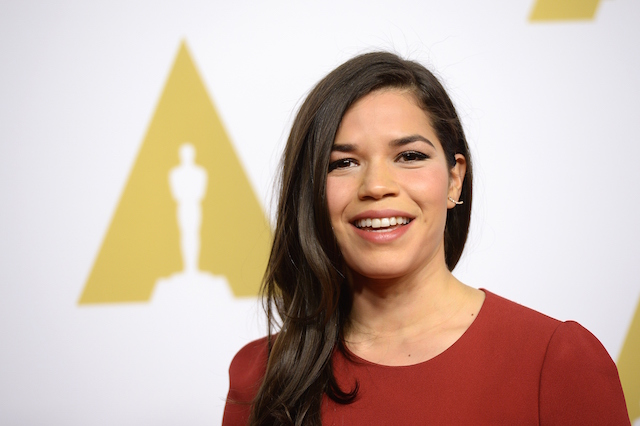 America Ferrera smiling in a red dress.