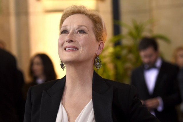 Meryl Streep looking upwards as she walks out of a building.
