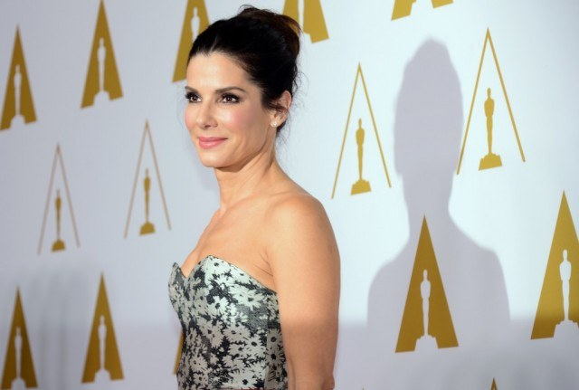 Sandra Bullock poses for the paparazzi in a floral strapless dress.