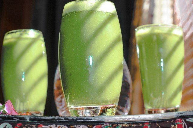 Several glasses of green smoothie arranged on a tray.
