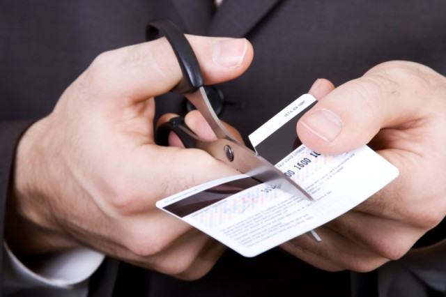A man cutting up a credit card with scissors