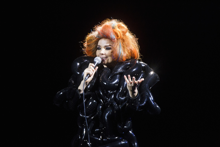 Bjork is on stage in a big black dress and an orange wig.