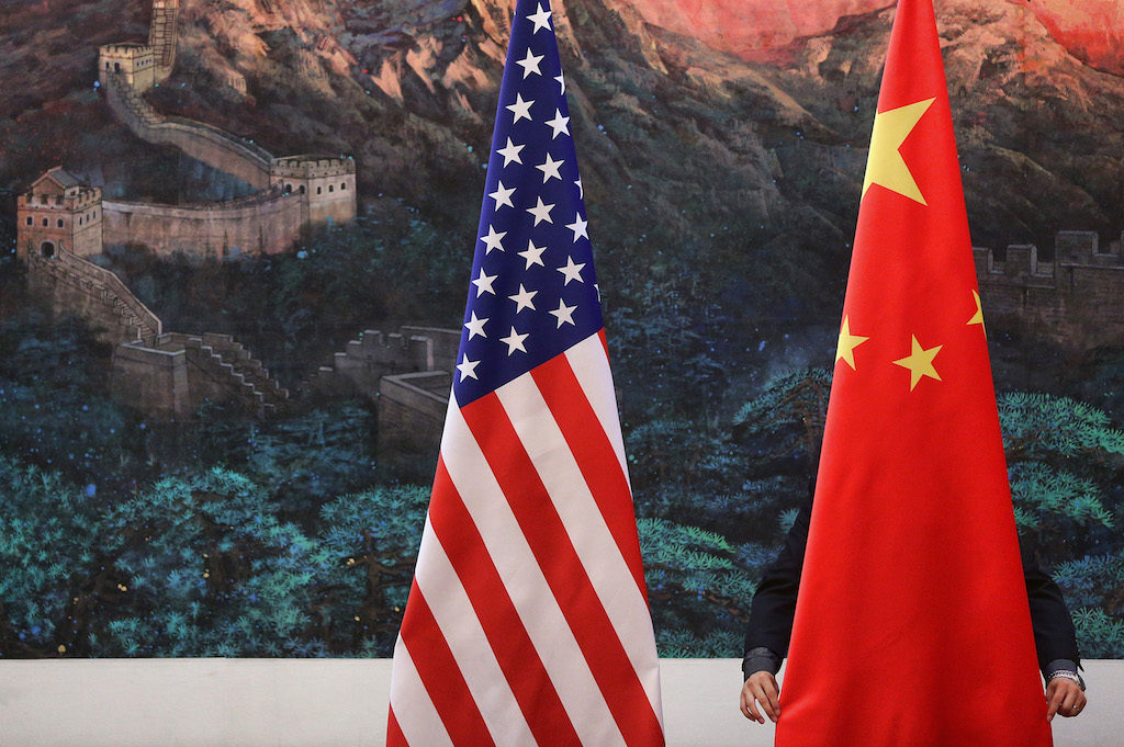 A Chinese man adjusts a Chinese flag, situated next to an American flag