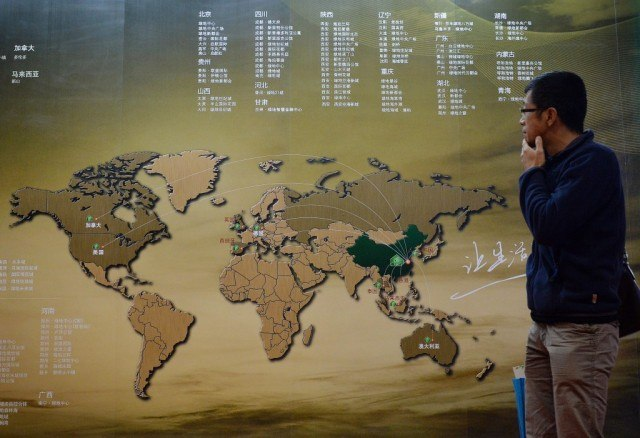 A Chinese investor walks past an investment map showing suitable property markets for wealthy Chinese to invest in at the International Property Expo in Beijing on April 11, 2014. Wealthy Chinese will pour AUD$44 billion (US$39.4 billion) into Australian real estate over the next seven years, potentially pushing prices in one of the world's most expensive housing markets even higher. Chinese property investors have been on a international spending spree since the global financial crisis hit most of the world's economies. Photo by Mark Ralston/AFP/Getty Images