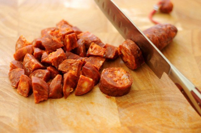 Cutting cured chorizo on a cutting board