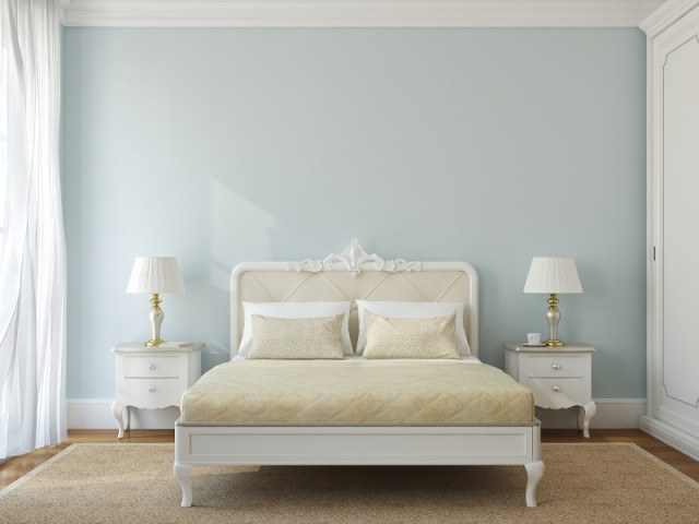 A bedroom with a blue wall, white bed, and tables with lamps.