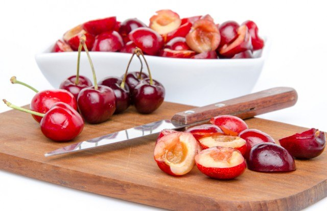 pitting and halving cherries on a cutting board