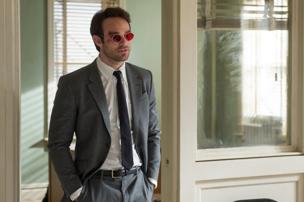 Charlie Cox wearing red sunglasses and a suit standing in a doorway as Matt Murdock on Daredevil