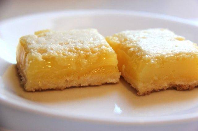 homemade lemon bars dusted with powdered sugar on a plate