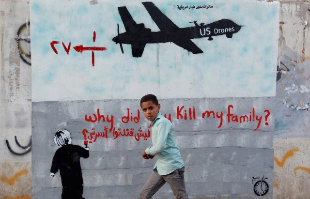 A Yemeni boy (C) walks past a mural depicting a US drone and reading ' Why did you kill my family' on December 13, 2013 in the capital Sanaa. A drone strike on a wedding convoy in Yemen killed 17 people, mostly civilians, medical and security sources said, adding grist to mounting criticism of the US drone war. (Photo by Mohammed Huwais/AFP/Getty Images)