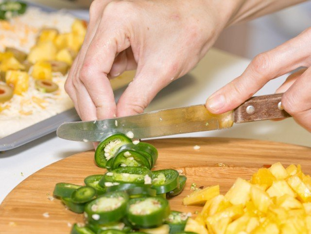 Cutting, chopping, jalapeno, pineapple on wooden board preparing food