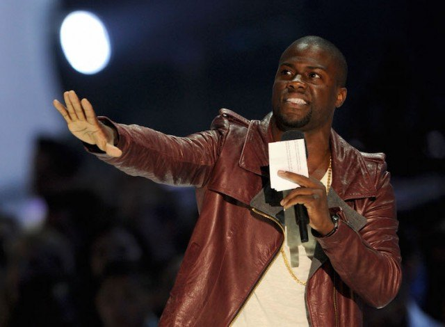 Kevin Hart extends one arm forward as he holds a microphone with his hand.