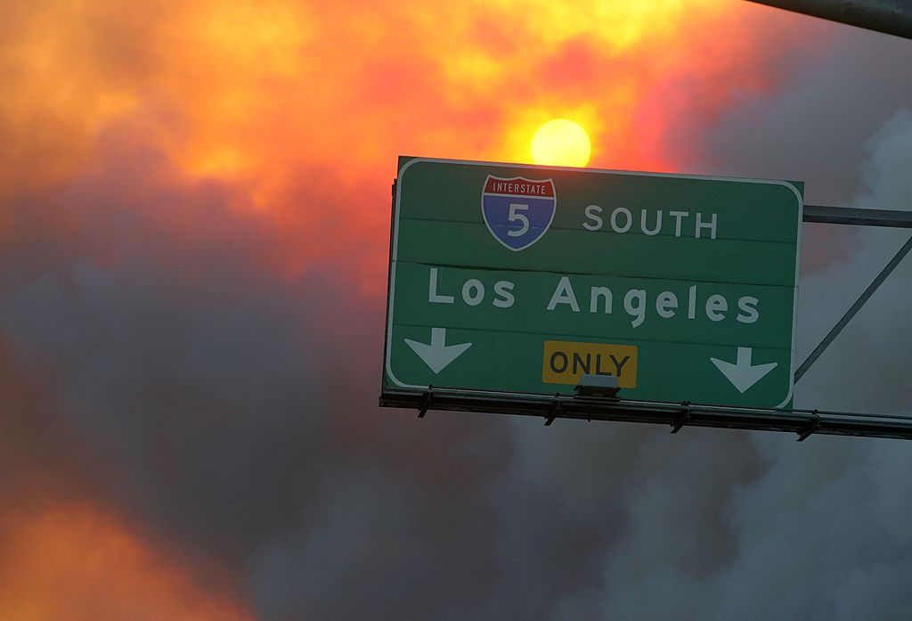 Smoke billows above a highway sign