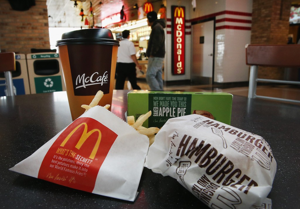 In this photo illustration, customers order food from a McDonald's restaurant on October 24, 2013 in Des Plaines, Illinois. McDonald's has announced it will make changes to its low-priced Dollar Menu, which includes items like coffee, small fries, hamburgers and apple pies. The new menu, dubbed the Dollar Menu and More, will offer some higher priced options such as the grilled Onion Cheddar Burger and a McChicken sandwich. (Photo Illustration by Scott Olson/Getty Images)